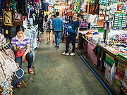 18 APRIL 2015 - BANGKOK, THAILAND:  A vendor checks her smart phone in the Chatuchak Weekend Market in Bangkok. Chatuchak Weekend Market in Bangkok is reportedly the largest market in Thailand and the world's largest weekend market. Frequently called J.J., it covers more than 35 acres and contains upwards of 5,000 stalls.       PHOTO BY JACK KURTZ