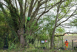 Harefield, UK. 27th April 2019. A security guard observes an environmental activist from Colne Valley Action standing in a tree to prevent its felling as part of work scheduled for this weekend for the HS2 project. The Colne Valley is an area of natural beauty and large areas of trees have been felled there for HS2 in recent weeks. Protesters based at the Harvil Road Wildlife Protection Camp are seeking to prevent further destruction.