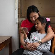 Vanessa Mae Rodel, 42, cuddles her seven-year-old daughter Keana Nihinsa, in their Hong Kong home, on March 21, 2019, days ahead of their move to Canada. / Photo: Maria de la Guardia