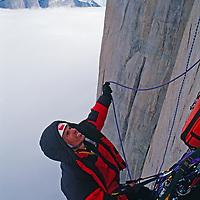 A rock climber belays above foggy Stewart Valley, high on Great Sail Peak.