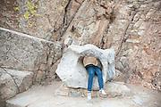 Julia Wentzel's legs hang out of a hole in a rock in Boulder Canyon, near Boulder, Colorado.