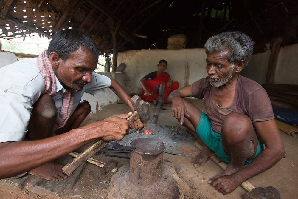 CAPTION: Rajashetty, who contracted polio early in life, is a self-employed blacksmith. He is pictured here working alongside two of his family members. He is a member of his local self-help group (SHG), which has enabled him to draw small loans to invest in his business. LOCATION: Alduru (village), Santhemarahalli (hobli), Chamrajnagar (district), Karnataka (state), India. INDIVIDUAL(S) PHOTOGRAPHED: From left to right: Rajashetty, Bhagya and Basavashetty.