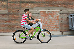 Teenage girl and teenage boy cycling