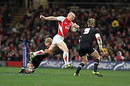 Tom Shanklin of Wales (c) tries to escape the clutches of Daniel Braid of the Allblacks. Invesco Perpetual match, Wales v New Zealand at the Millennium stadium in Cardiff on Sat 27th Nov 2010.  pic by Andrew Orchard, Andrew Orchard sports photography,