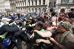 © Licensed to London News Pictures. 19/07/2021. London, UK. Protesters clash with police in Parliament Square in central London on Freedom Day. All covid regulations in England are being scrapped from today even though infections and hospitalisations are on the increase. Photo credit: Peter Macdiarmid/LNP
