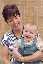 Mother holding baby on knee smiling,