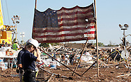 The American flag from the Plaza Towers elementary school is erected on pole in front of whats left of the school in Moore, Oklahoma May 22, 2013. A massive tornado tore through a suburb of Oklahoma City, wiping out whole blocks and killing at least 24.   REUTERS/Rick Wilking (UNITED STATES)