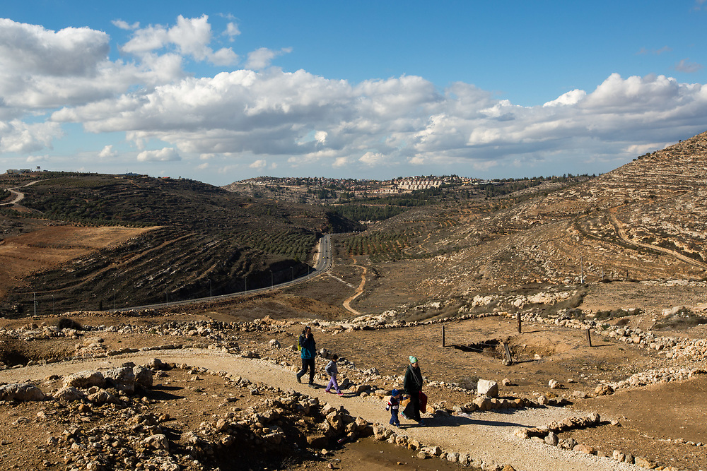 The West Bank Jewish settlement of Eli is seen in the background as Israelis visit the archaeological park of Ancient Shiloh, which is located at the entrance to the modern Jewish settlement of Shiloh, south of the Palestinian West Bank town of Nablus, on January 1, 2017. Shiloh was the religious capital of Israel, an assembly place for the people of Israel and a center of worship before the first temple was built in Jerusalem. Its sacred area housed the Ark of Covenant.