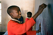 A school child writing on the blackboard during class at Ikuna village primary school, near to Iringa in Tanzania. They are having a class run by a Student Partnerships Worldwide (SPW) volunteer.