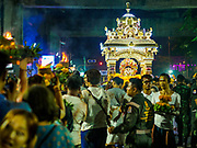 30 SEPTEMBER 2017 - BANGKOK, THAILAND: People run into the street to see the chariot bearing the deity during the Navratri parade in Bangkok. Navratri is a nine night (10 day) long Hindu celebration that marks the end of the monsoon and honors of the divine feminine Devi (Durga). The festival is celebrated differently in different parts of India, but the common theme is the battle and victory of Good over Evil based on a regionally famous epic or legend such as the Ramayana or the Devi Mahatmya. Navratri is celebrated throughout Southeast Asia in communities that have large Hindu population. Bangkok's celebration of Navratri was subdued this year because Thais are still mourning the death of Bhumibol Adulyadej, the Late King of Thailand, who died on October 13, 2016.      PHOTO BY JACK KURTZ