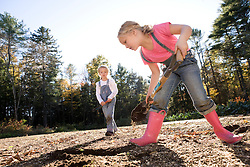 two young sisters work and play in the sunshine on family farm in the Fall