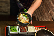 A server garnishing a bowl of Tasmanian ocean trout and wild mushroom rice pot.