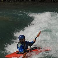 Kayaker David Manning plays in waves on the Kananaskis River in the Canadian Rockies near Calgary, Alberta.