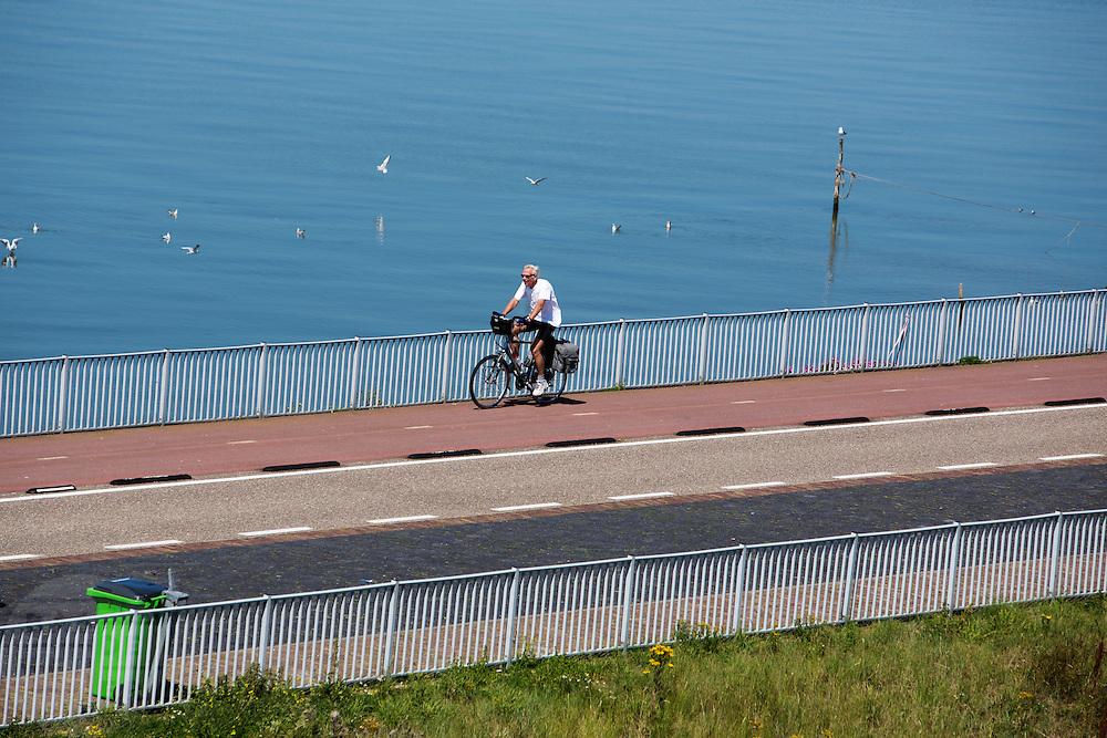 Fietsers rijden over de Afsluitdijk. In 1932 werd de opening tussen de Waddenzee (achtergrond) en de toenmalige Zuiderzee gesloten. Nu is het een belangrijke verkeersader tussen Friesland en Noord-Holland en scheidt het de Waddenzee met het IJsselmeer.<br /> <br /> Cyclists are riding on the Afsluitdijk. In 1932, the gap between the Wadden Sea and the former Zuiderzee closed by the Afsluitdijk. Now it is a major thoroughfare between Friesland and North Holland and it separates the Wadden Sea from the IJsselmeer.