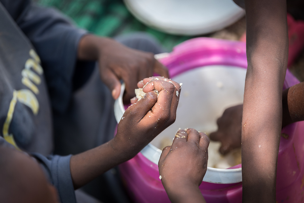31 May 2019, Mokolo, Cameroon: A grou of children enjoy a meal in one of the sites for internally displaced people in Zamay. One of 20 sites for Internally Displaced People in the Far North region of Cameroon, Zamay currently hosts 4,102 IDPs from the border area between Nigeria and Cameroon. Fleeing the atrocities of Boko Haram, and cross-border fighting between Boko Haram and Cameroonian coalition forces, the IDPs have settled alongside the host community of 32,000 people in Zamay.