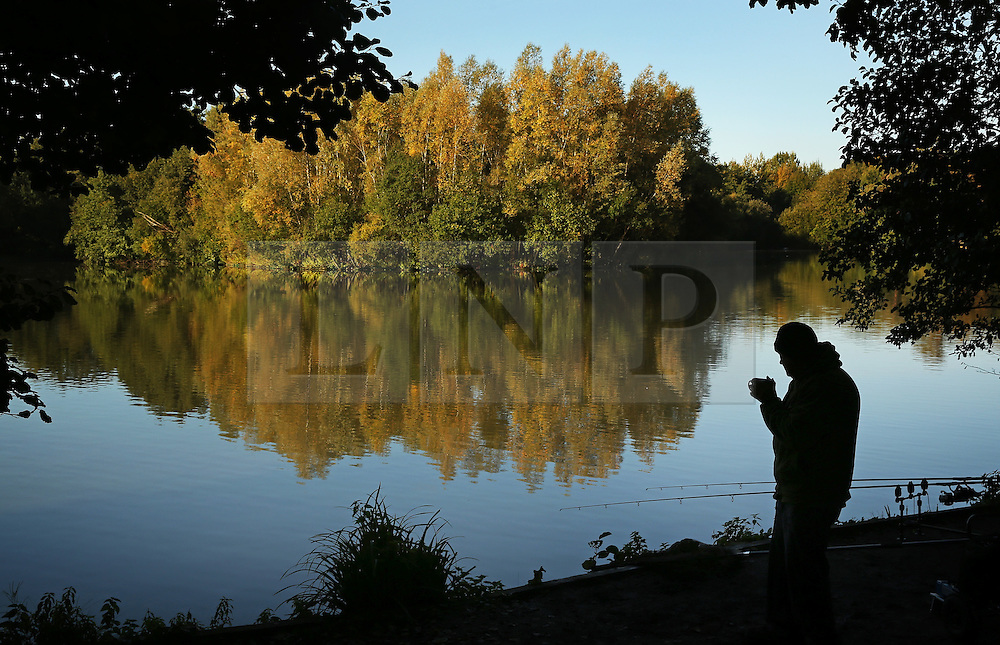 © Licensed to London News Pictures. 08/10/2015. Godalming, UK. A fisherman takes a tea break on the banks of Broadwater Lake as early morning sunshine illuminates the trees.  Photo credit: Peter Macdiarmid/LNP