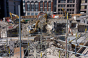 Demolition site by contractor Erith at the northern end of London Bridge, City of London. Looking down from a high position on London Bridge, we see the width of this former office building site that is now a heap of rubble, contrte and twisted metal being cleared for a future redevelopment. Heavy machinery by contractor Erith is op[erating to clear the site before the new architecture replaces the eighties design. Walkways have been placed for safety and scaffolding supports weakened structures.