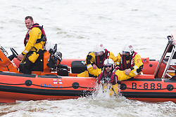 © Licensed to London News Pictures. 15/05/2016. Brighton, UK. Members of the Brighton RNLI lifeboat crew haul a colleague aboard after he delivered ice creams for his team mates who are patrolling the sea off Brighton. Photo credit: Hugo Michiels/LNP