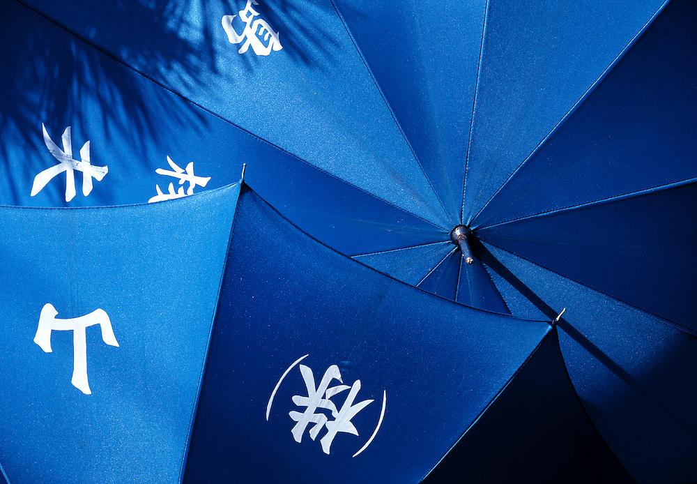 Blue umbrellas dry in the bright sun on Miyajima Island, Japan.
