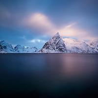 Winter sunrise on snow covered Olstind mountain peak rising from Fjord, Toppøya, Moskenesøy, Lofoten Islands, Norway