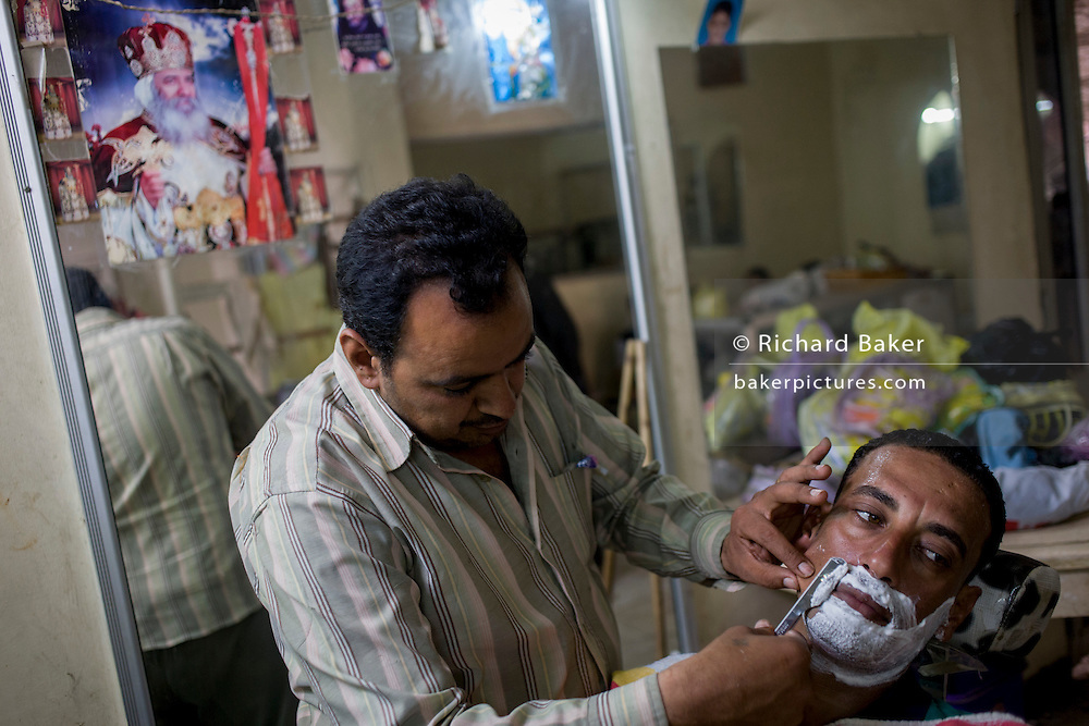 A young Egyptian man has a shave from the local barber in Bairat, a village on the West Bank of Luxor, Nile Valley, Egypt.