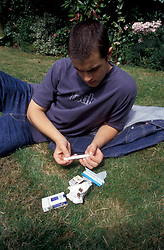 16 year old youth rolling a joint UK. Posed by model