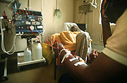 Elderly patients undergo Hemodialysis (a blood purifying treatment.) in the renal unit at St Bartholomews (Barts) Hospital in Smithfield, The City of London, England. A female woman is in the background laying back in a comfortable armchair while in the foreground a man has his left arm resting on his knee with connecting tubes that feeds his blood by vascular access from the body into the dialyzer, a machine that filters the purified blood due to the patient's renal (kidney) failure. It is a bright room and many other machines are operating in this manner. Three quarters of the UK's 19,000 dialysis patients receive haemodialysis rather than peritoneal dialysis, where a sterile solution containing minerals and glucose is run through a tube straight into the intestine.