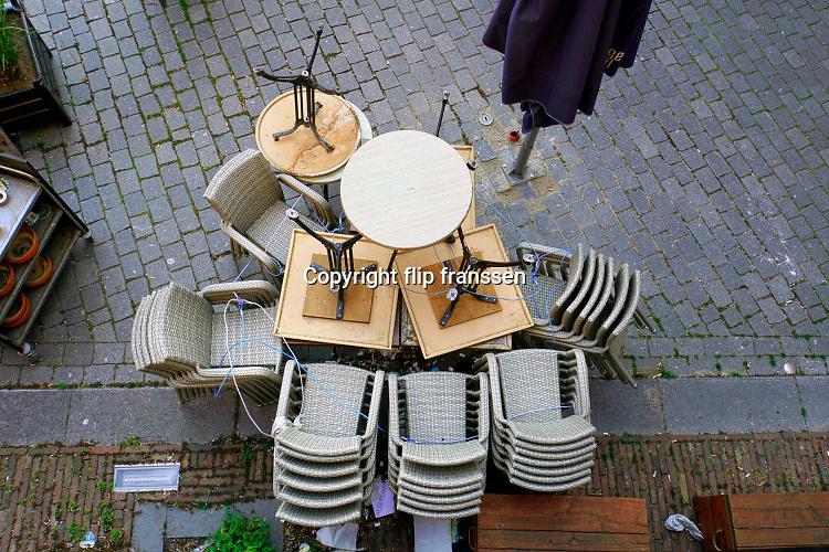 Nederland, Nijmegen, 26-4-2020 De horeca is al enkele weken gesloten vanwege de coronadreiging en veel ondernemers willen dat de regering het normale dagelijks leven weer langzaam laat opstarten . Opgestapelde stoelen . Unlock,beperkende,opheffen,versoepelen,versoepeling . Foto: Flip Franssen