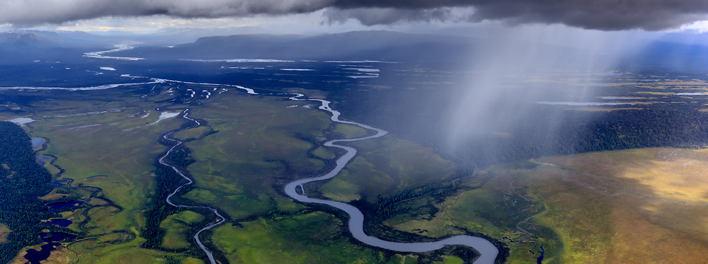 Aerial panoramic of rain shower over braided rivers and colorful valley below
