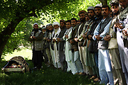 Male members of the village and the family pray before the dead body of Qamar, center, a 26-year-old tuberculosis patient who died of postpartum complications two weeks after the delivery, before the burial, Shohada district in Badakshan province, Afghanistan, Monday, May 21, 2007. No females were allowed to attend the funeral.