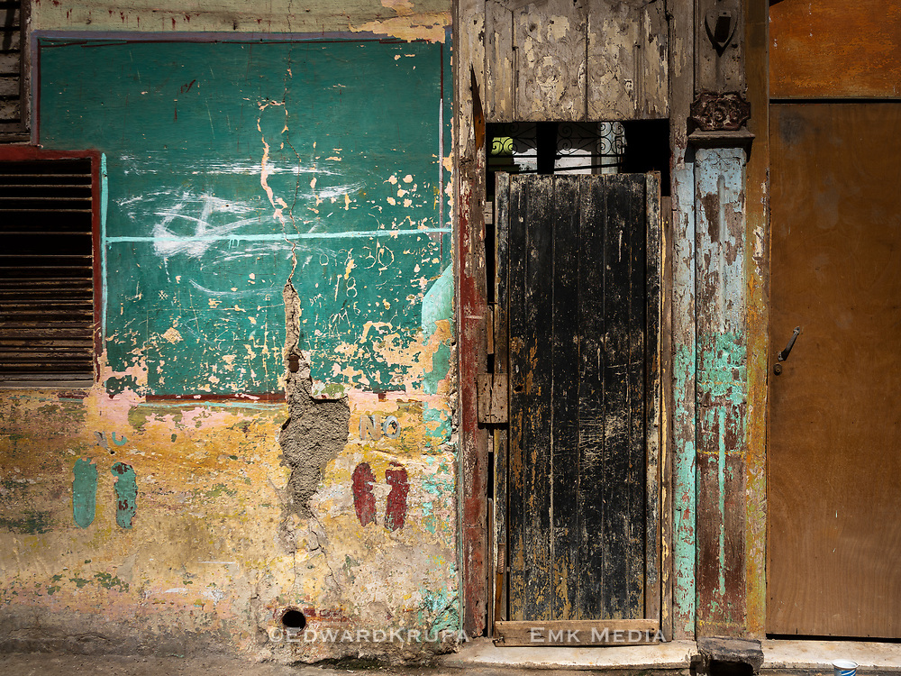 Building exterior with doors, lots of paint layers, materials and  markings in Havana Centro.