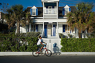 A boy on a bicycle in front of a colonial style house in Dunmore Town,<br /> Harbour Island, The Bahamas