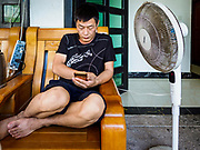"""14 FEBRUARY 2019 - SIHANOUKVILLE, CAMBODIA:  A man who works for a Chinese enterprise in Sihanoukville checks his smart phone in front of his apartment building. There are thousands of Chinese workers in Sihanoukville who work to support the casino and hotel industry in the town. There are about 80 Chinese casinos and resort hotels open in Sihanoukville and dozens more under construction. The casinos are changing the city, once a sleepy port on Southeast Asia's """"backpacker trail"""" into a booming city. The change is coming with a cost though. Many Cambodian residents of Sihanoukville  have lost their homes to make way for the casinos and the jobs are going to Chinese workers, brought in to build casinos and work in the casinos.      PHOTO BY JACK KURTZ"""