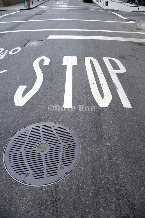 stop signal on asphalt at an intersection with a Con Edison metal street cover New York