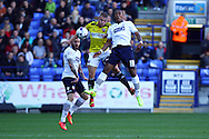 Brentfords' Jake Bidwell jumps for the ball with Bolton Wanderers' Neil Danns. Skybet football league championship match, Bolton Wanderers v Brentford at the Macron stadium in Bolton, Lancs on Saturday 25th October 2014.<br /> pic by Chris Stading, Andrew Orchard sports photography.