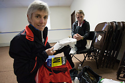 """Joan Samuelson prepares for race in elite athlete's holding area with daughter, Abby, holding cap with """"will power"""" written on it"""