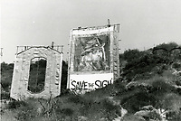 """1973 A """"save the sign"""" banner featuring Leon Russell covers the letter D of the Hollywood sign."""
