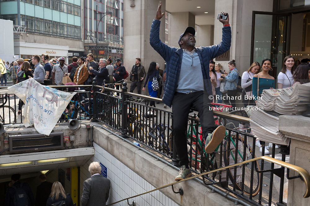 As activists with Extinction Rebellion protest about climate change in a blocked-off Oxford Circus a newspaper vendor sings to the DJ's music, on 17th April 2019, in London, England.