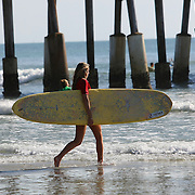 A female long boarder takes to the water during the 28th annual National Kidney Foundation, Rich Salick Pro/Am surf festival takes place at the the Cocoa Beach pier on Saturday,  September 2, 2013 in Cocoa Beach, Florida. This event raises thousands of dollars for people with kidney disease and also benefits the services of the NKF of Florida. (AP Photo/Alex Menendez)