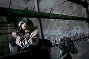 An Afghan miner brushes his hair inside a hammam, a public shower, at Karkar Coal Mine.