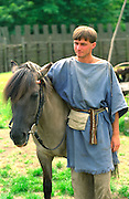 Actor age 23 standing with pony. Ancient Slavic Settlement Biskupin Poland
