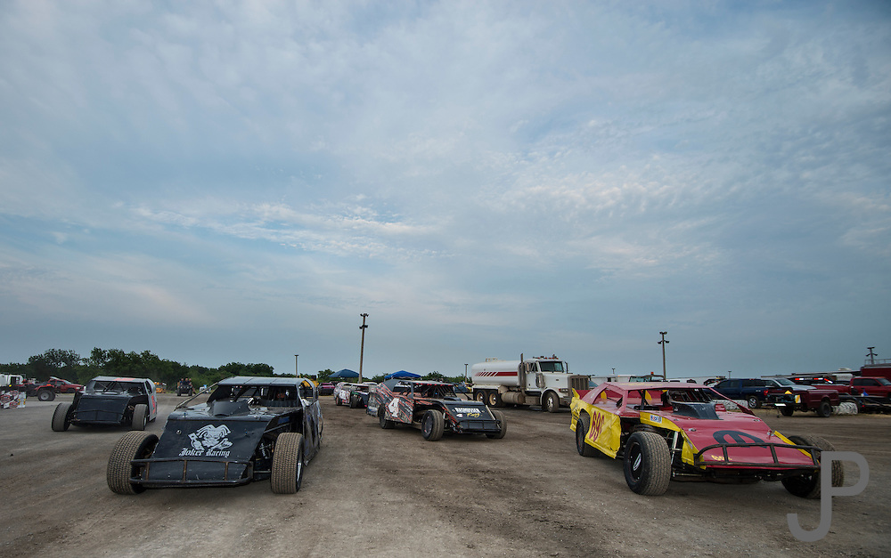 Modified stock cars line up waiting to enter the track for their qualifying runs.