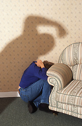 Young woman cowering behind sofa as abuser prepares to beat her,