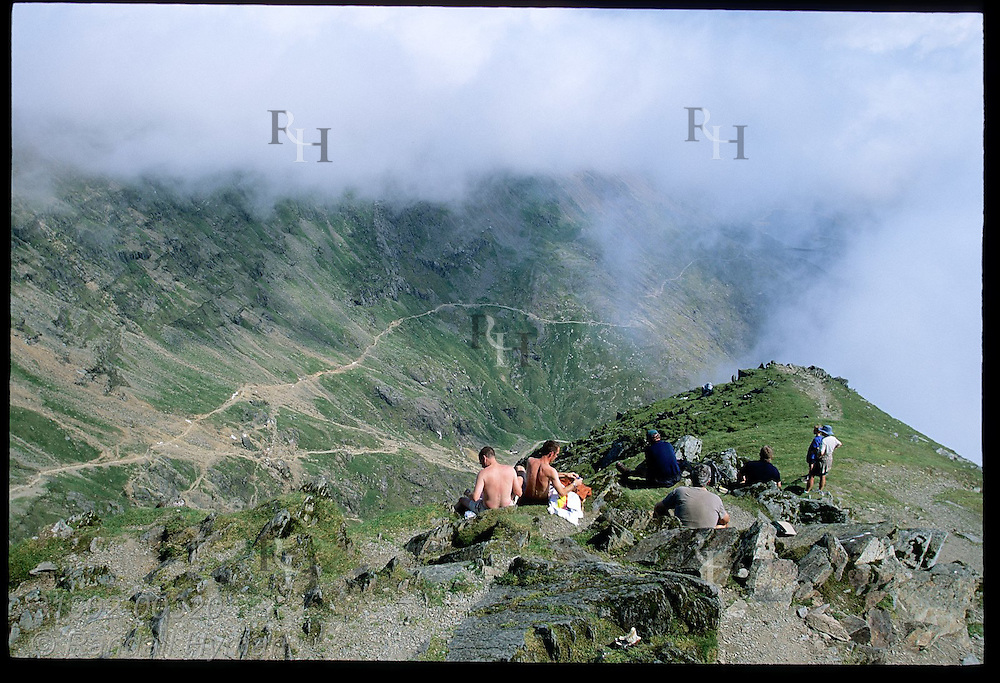 Hikers sit atop Mount Snowdon (3560') enjoying view of Pyg Track and distant clouds in August; Snowdonia National Park, Wales.
