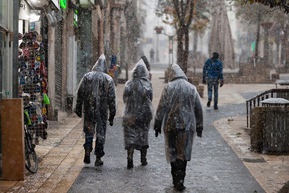 People covered with plastic coats to protect themselves from the rain and snow, are seen while walking up Ben Yehuda Street, as snow falls during a winter storm in Jerusalem, Israel, on January 7, 2015.