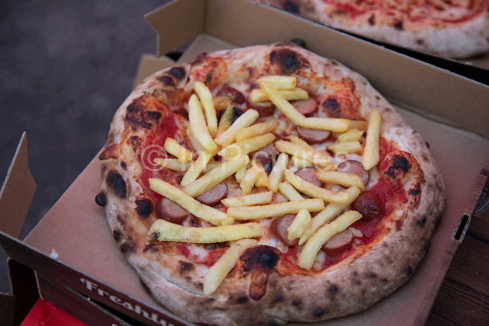 Chip topped pizza in London, England, United Kingdom. Pizzas rarely are seen to go for double carbohydrates, but this is an exception.