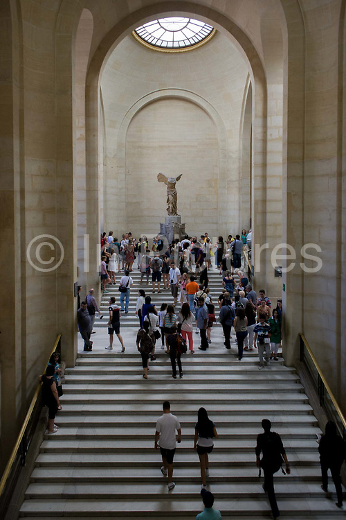 Tourists walk towards The Winged Victory of Samothrace, also called the Nike of Samothrace, a 2nd century BC marble sculpture of the Greek goddess Nike (Victory). Since 1884, it has been prominently displayed at the Louvre and is one of the most celebrated sculptures in the world. The Musée du Louvre is one of the world's largest museums, the most visited art museum in the world and a historic monument. A central landmark of Paris, France, it is located on the Right Bank of the Seine in the 1st arrondissement (district). Nearly 100,000 objects from prehistory to the 19th century are exhibited over an area of 60,600 square metres (652,300 square feet).