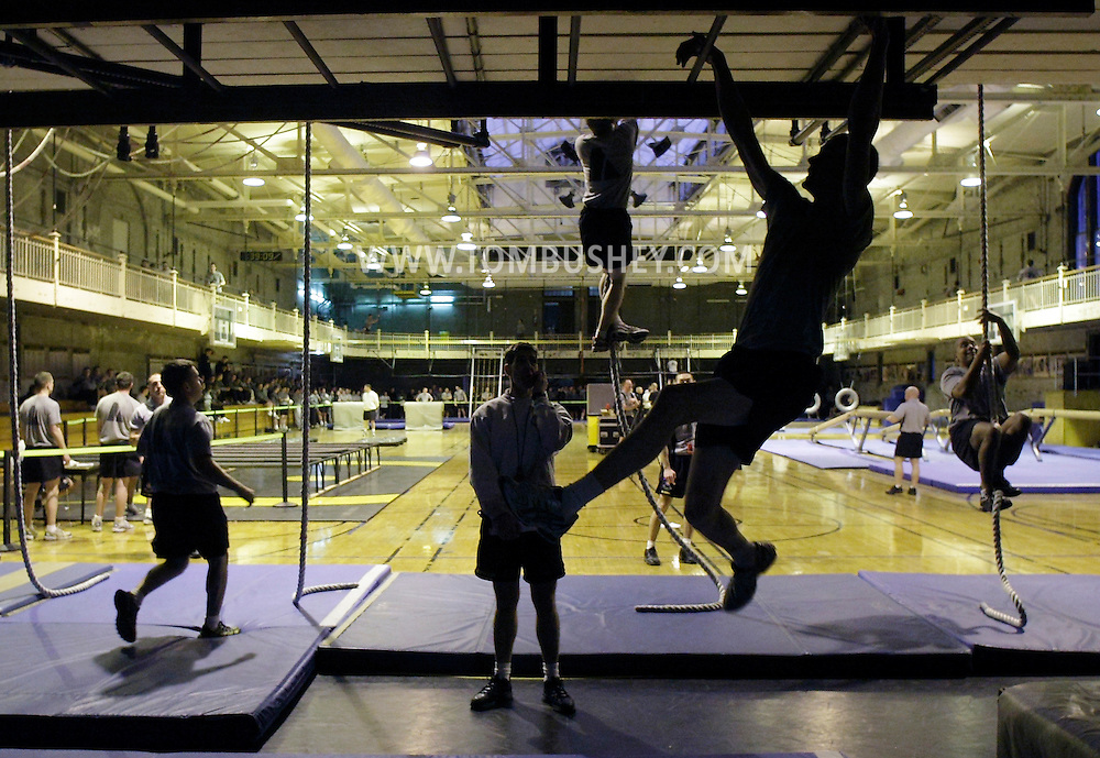 A cadet, in foreground, moves across the rungs of the horizontal ladder as other cadets start the rope climb while taking the Indoor Obstacle Course Test in Hayes Gym at the U.S. Military Academy at West Point on Feb. 9, 2010.