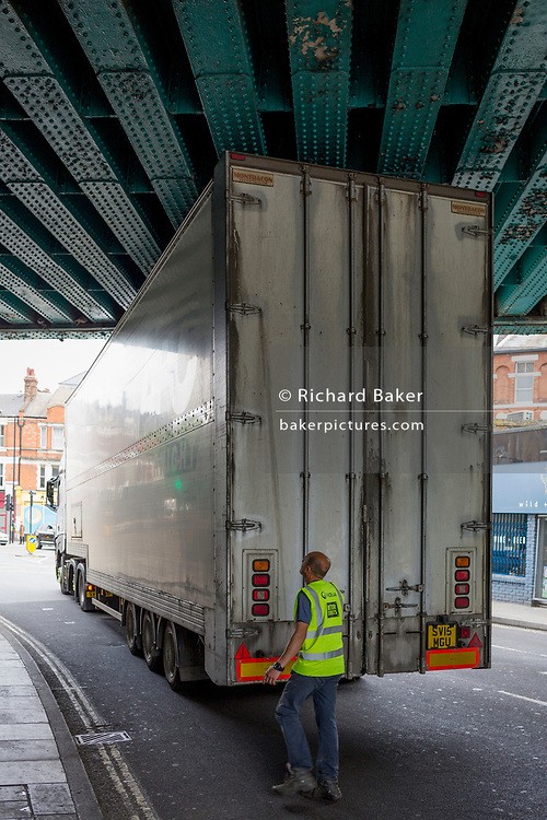 A high-sided HGV lorry squeezes under the railway bridge over the A215 at Herne Hill, on 7th June 2018, in south London, England.