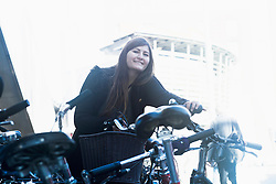 Young woman standing with bicycle in parking lot, Freiburg im Breisgau, Baden-Württemberg, Germany